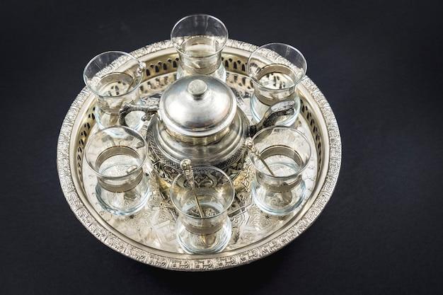 Металлическая кружка и турецкие хрустальные бокалы на круглом подносе Premium Фотографии