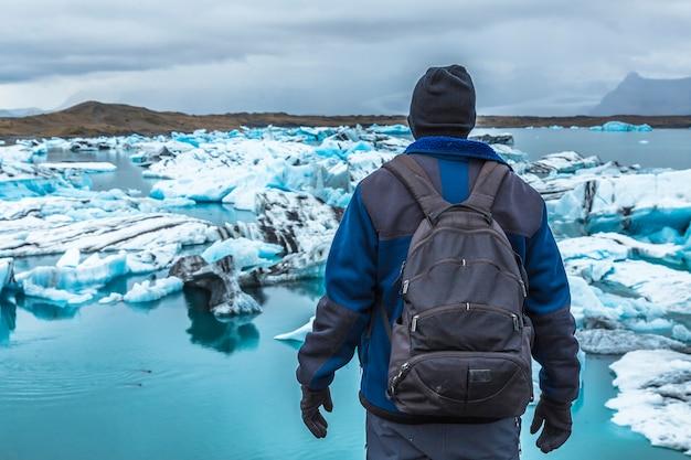 アイスランド南部の金色の輪にある手配氷河を眺めるバックパックを持つ若者 Premium写真