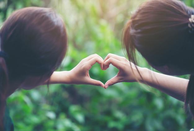 Женщины, делающие сердечки своими руками Premium Фотографии