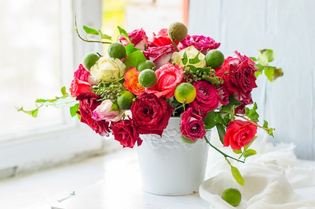 Красные розы в белой вазе Premium Фотографии