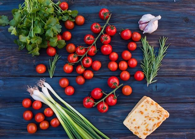 Вишня, зеленый зеленый лук, зеленый розмарин, листья кориандра, сладкий сыр, чеснок на темном деревенском деревянном фоне Premium Фотографии