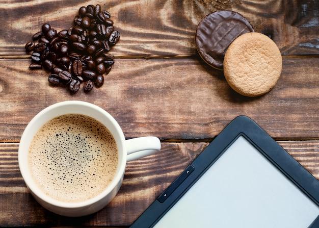泡、電子ブック、ケーキ、木製のテーブルにハート型のコーヒー豆とコーヒーのキャップ Premium写真