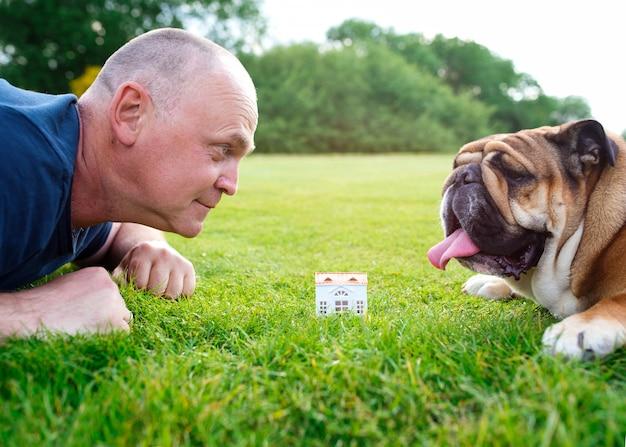 人と犬が公園の緑の芝生の上のおもちゃの家を見て Premium写真