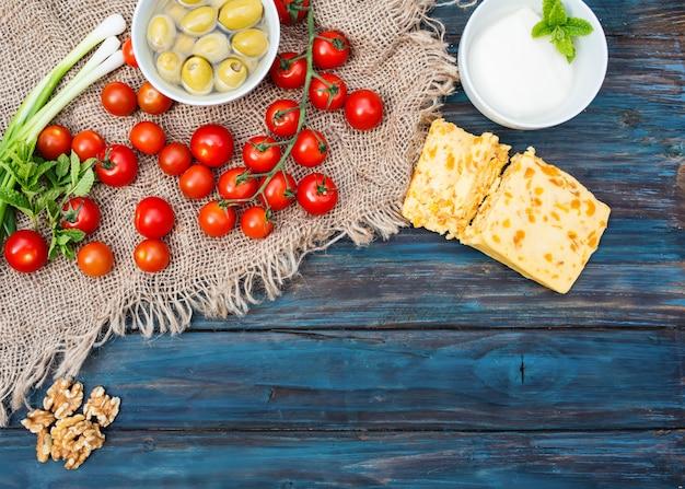 Некоторые красные свежие вишни, зеленый лук, кориандр, сыр, чеснок, оливки в миске, хлеб на темном деревенском деревянном фоне Premium Фотографии