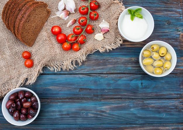 Вишня, зеленый лук, кориандр, сыр, чеснок, оливки в миске, хлеб на темном деревенском деревянном фоне. Premium Фотографии