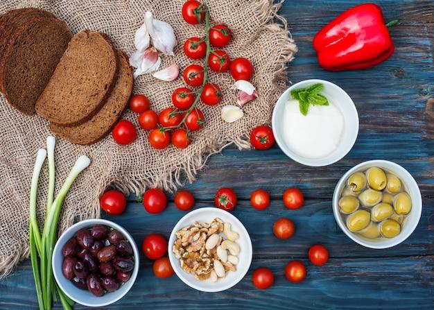 Вишня, зеленый лук, кориандр, сыр, чеснок, оливки в миску, хлеб, сладкий перец на темном деревенском деревянном фоне Premium Фотографии