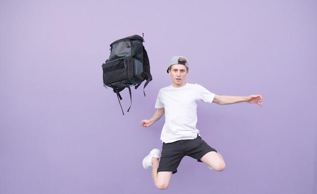Человек в белой футболке прыгает с рюкзаком на фиолетовом фоне Premium Фотографии