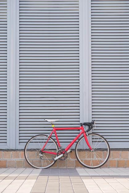 赤いロードバイクは灰色の壁の上に立つ Premium写真