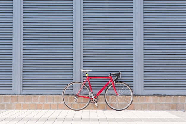 道路の赤い自転車は灰色の壁の上に立つ Premium写真