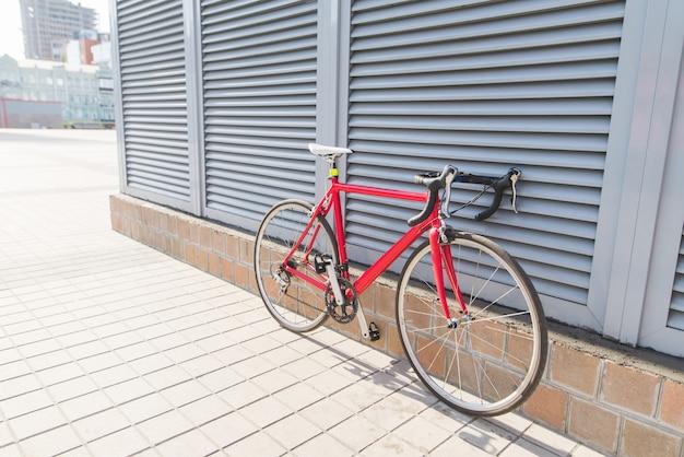 灰色の壁の近くに立つ美しい赤いロードバイク Premium写真