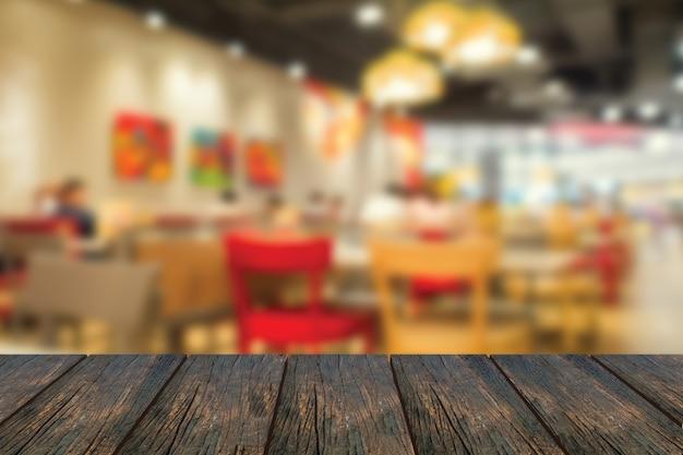 フォアグラウンドで木製のテーブルとレストランの中をデフォーカスします。 Premium写真