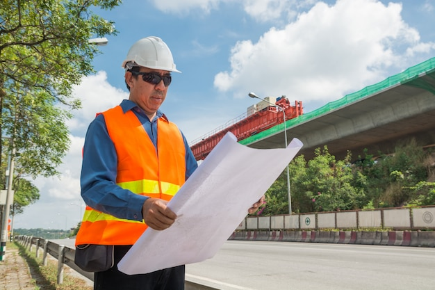 エンジニアまたは建築家が作業または読書の白いヘルメットを着用 Premium写真