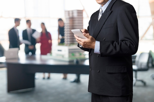 ビジネスマンが会議室でワイヤレスモバイルスマートフォンデバイスを使用します。 Premium写真