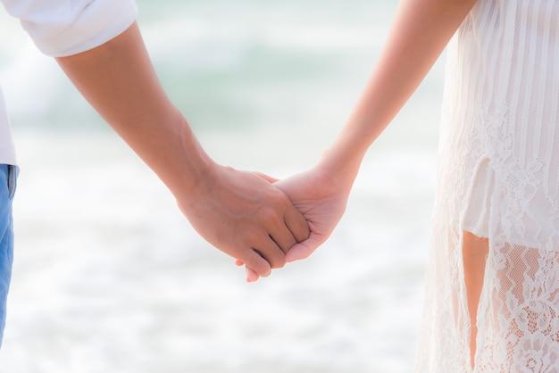 香りのカップル夏休み、アジアの若い女性がビーチで人の手を持って、幸せと恋に Premium写真