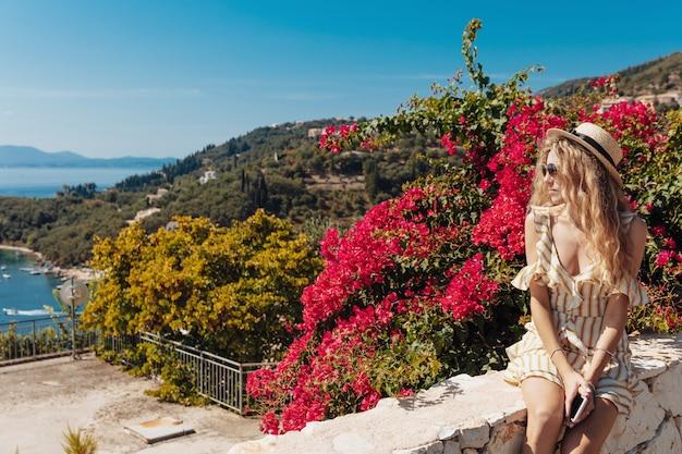 Вид сбоку блондинке, глядя на удивительный морской пейзаж Premium Фотографии