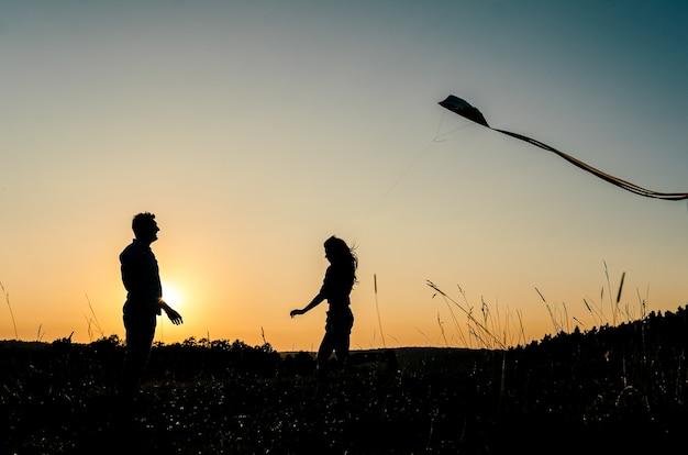 Счастливая милая пара в силуэт летающих змей на открытом воздухе Premium Фотографии