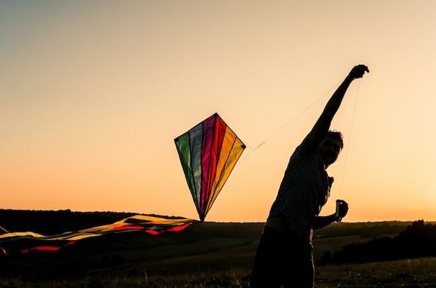 Молодой человек начинает летать красочный змей в закатном небе Premium Фотографии