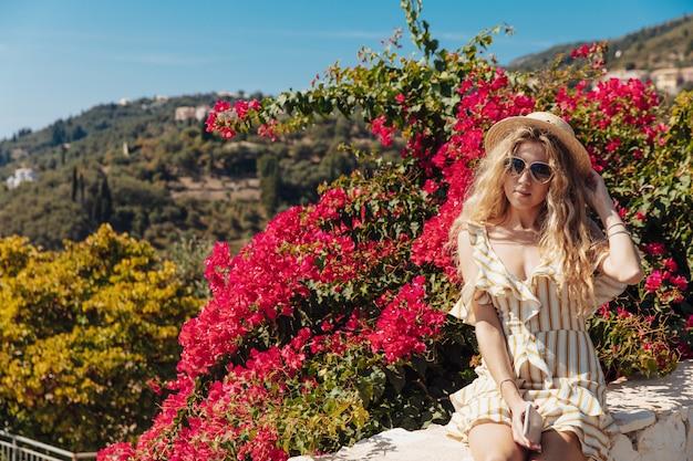 Блондинка сидит на дороге границы с потрясающим видом позади Premium Фотографии