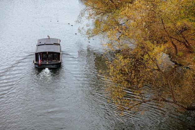 Темная деревянная лодка, идущая с потоком реки Premium Фотографии