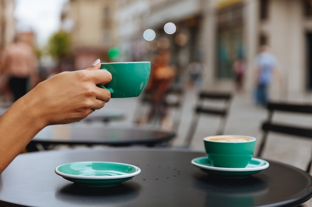Крупным планом женщина рука голубая чашка горячего кофе Premium Фотографии