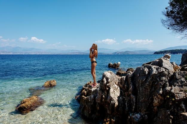 Привлекательная дама в черном бикини, стоя на скалах у моря Premium Фотографии