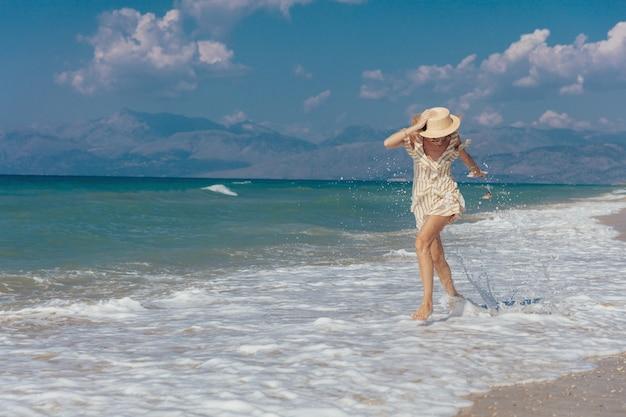 砂浜で裸足で歩く陽気な美しい少女 Premium写真