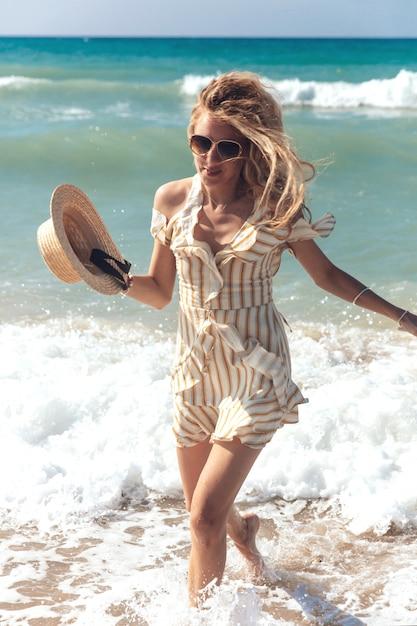 海でゾッとする縞模様のドレスで魅力的なブロンドの女性 Premium写真
