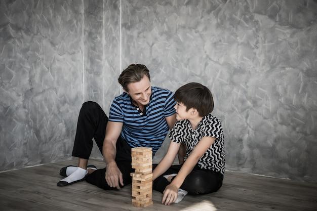 家の中でジェンガを演じる父と息子。幸せな家族のコンセプト。 Premium写真