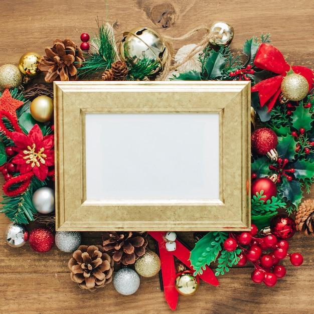 クリスマスのフォトフレームは、木製のテーブルに装飾とテンプレートをモックアップ。 無料写真