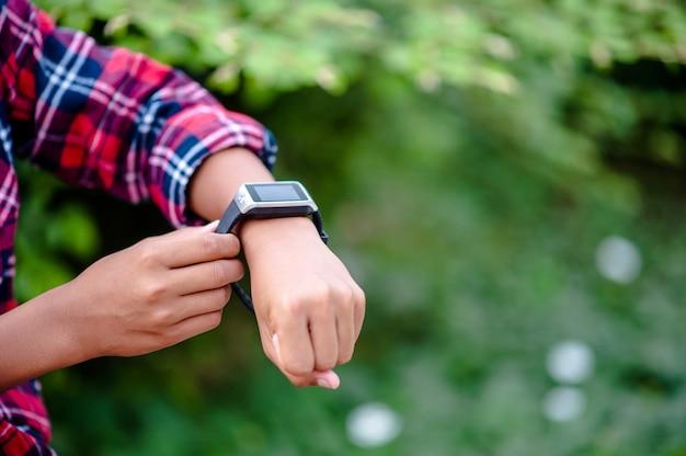 男の子の手やデジタル時計腕時計を見る。方向は定刻です。 Premium写真