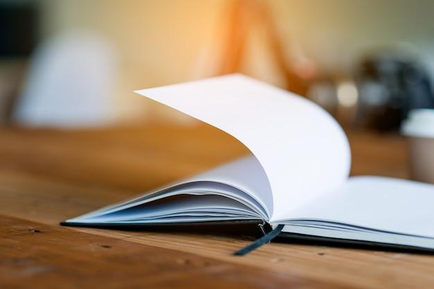 本はビジネスデスクに置かれます。コピースペースで読むことの概念。 Premium写真