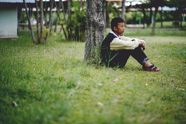 悲しいことに森の中で一人で座っている少年の写真うつ病の概念 Premium写真