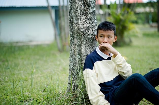 Картина молодого мальчика, сидящего в ожидании кого-то ожидание концепции Premium Фотографии