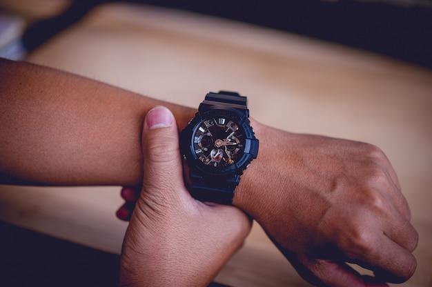 手と男性の黒い腕時計、時間厳守の概念 Premium写真