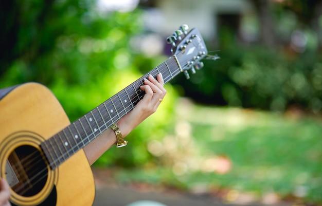 ミュージシャンの手とアコースティックギター Premium写真