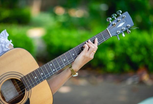 ミュージシャンの手とアコースティックギター、非常に良い音の楽器 Premium写真
