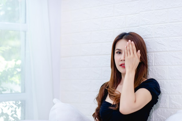 白い部屋で孤独な目を閉じて微笑んでいる女の子のクローズアップショット Premium写真