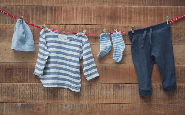 赤ちゃんの服は洗濯ラインと木製の背景で乾燥していた Premium写真