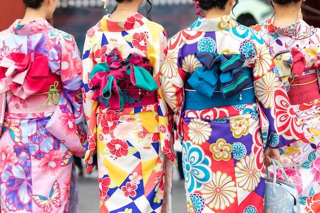 東京の浅草寺の前に日本の着物姿で立っている若い女の子 Premium写真