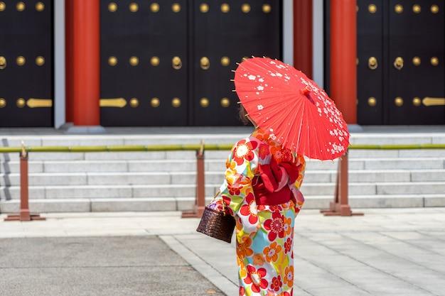 東京の浅草寺の前に日本の着物姿で身に着けている若い女の子、 Premium写真