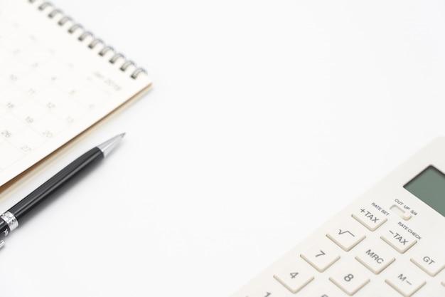 カレンダー、電卓ペンおよび他のオフィスのあるトップビューオフィステーブルデスクのフラットレイアウト Premium写真