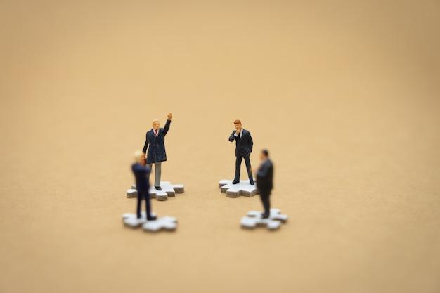 白いジグソーパズルの上に立ってミニチュア人ビジネスマン Premium写真