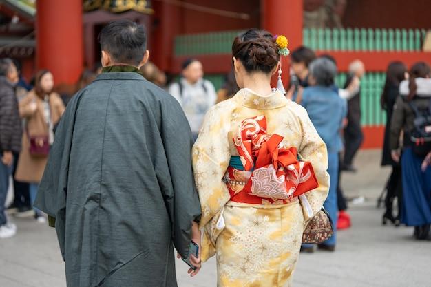 日本の東京の浅草寺の前に立っている日本の着物を着た少女。 Premium写真