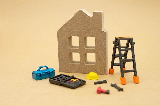 家のモデルと機器のモデル黄色いヘルメットのモデルがあります。 Premium写真