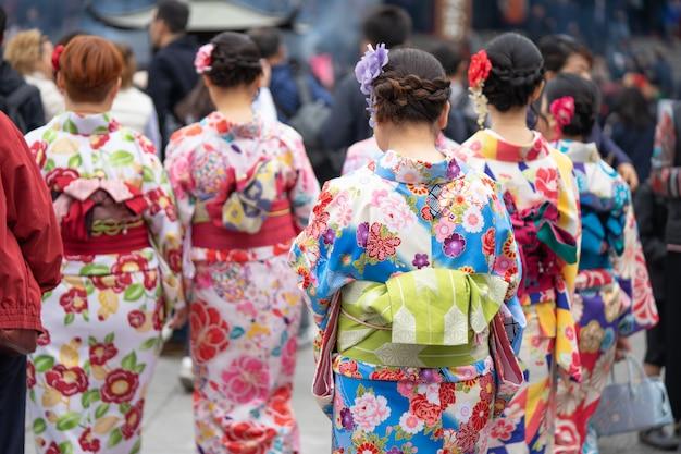 東京の浅草寺の前に立っている日本の着物を着た少女。 Premium写真