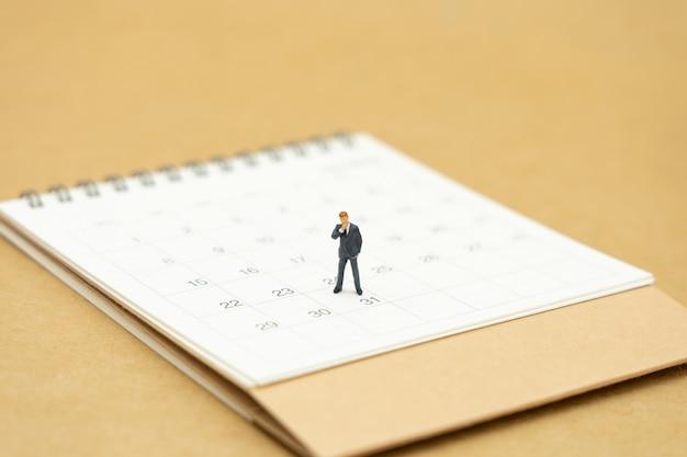 白いカレンダーの上に立っているビジネスマンのミニチュア Premium写真