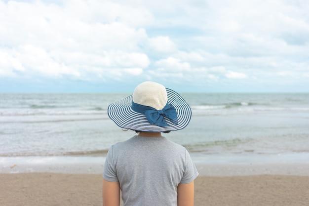 Азиатская молодая женщина стоя лицом к морю. Premium Фотографии