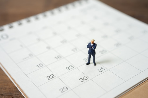 白いカレンダーの上に立ってミニチュアの人々ビジネスマン Premium写真