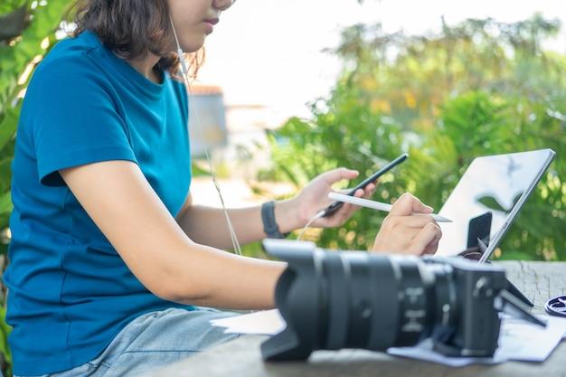Фотограф сидит и редактирует фотографии с помощью планшета. портативный размер, умные функции Premium Фотографии