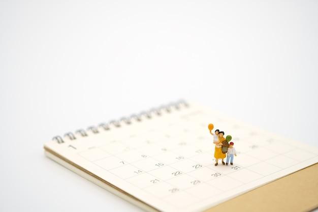 白いカレンダーに立っているミニチュアの人々 Premium写真